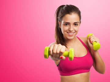 portraif of pretty young girl exercising wih weight